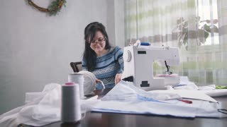 Attractive brunette female and sewing machine, dolly shot