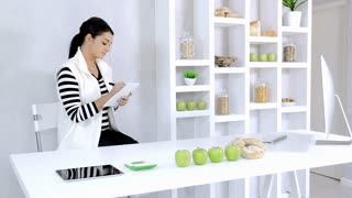 attractive brunette lab technician working with technology in the study of nutrition in food