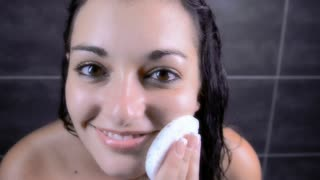 attractive brunette woman doing her daily cleansing routine in bathroom