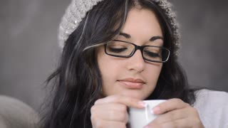 attractive brunette woman drinking coffee in her luxuary apartment