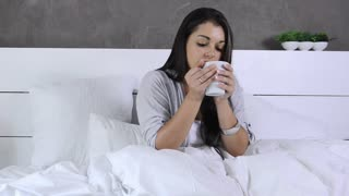 attractive brunette woman drinking coffee in luxury bedroom