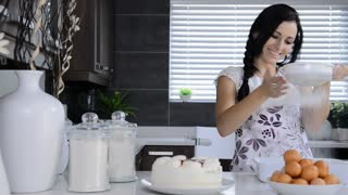 attractive brunette woman in modern kitchen baking muffins