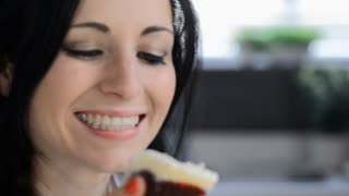 attractive brunette woman in modern kitchen eating cake