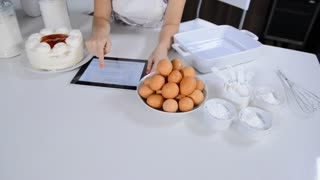 attractive brunette woman in modern kitchen using tablet computer while baking