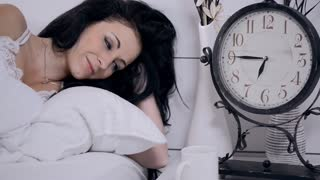 attractive brunette woman in white bed with coffee