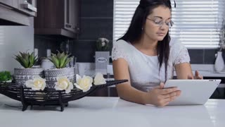 Attractive brunette woman using tablet computer retail internet surfing.