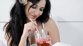 attractive brunette woman with flower in her hair drinking red juice in bedroom