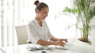 Attractive businesswoman sitting at table and using laptop