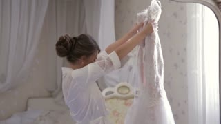 Attractive European bride is holding and checking her amazing wedding dress, she is pleased with result and tries it on. In mirror shooting. Inside bedroom shooting. Wedding atmosphere.
