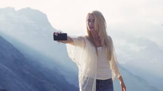 Attractive European girl with long blonde hair in jeans and white blouse is taking selfie on the highest peak of Switzerlands mountains chain in a bright sunlight. International tourism.
