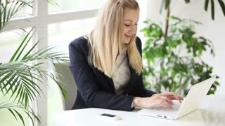 Attractive formaly dressed young woman using laptop and smiling at camera