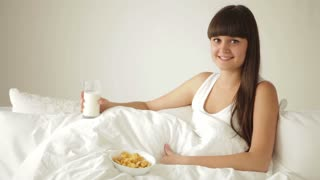 Attractive girl relaxing in bed drinking milk and eating cereal