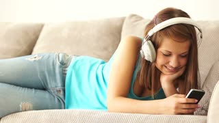 Attractive girl relaxing on sofa and listening to music with headset