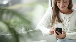 Attractive girl sitting by window using mobile phone looking at camera and smiling. Panning camera