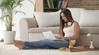 Attractive girl sitting on floor with laptop and drinking juice