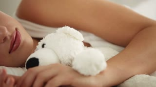 Attractive girl sleeping in bed and hugging teddy bear. Panning camera