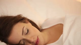 Attractive girl sleeping in bed waking and smiling at camera then falling asleep again. Panning camera