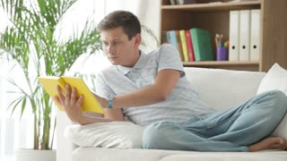 Attractive guy relaxing on sofa reading book and smiling at camera