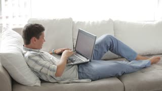 Attractive guy relaxing on sofa using laptop closing it and looking at camera