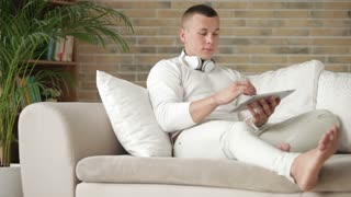 Attractive guy relaxing on sofa with touchpad and smiling at camera