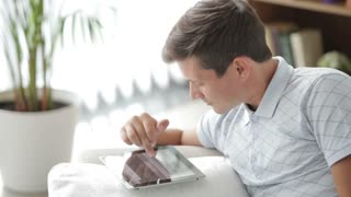 Attractive guy using touchpad eating apple and smiling at camera