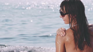 Attractive sunbathing young woman applying sunscreen to her shoulder on a warm sunny morning near the sparkling sea. Health and beauty concept. Slow motion. Filmed at 250 fps
