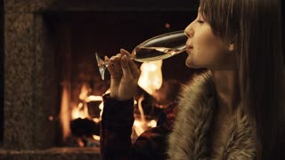 Attractive woman drinking champagne by the fireplace. Festive night by the fire. 4k graded from RAW, UHD, Ultra HD resolution.