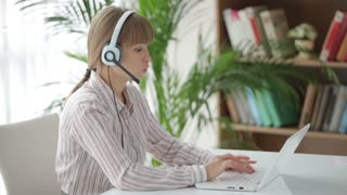 Attractive woman in headset sitting at table and working on laptop