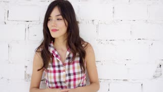 Attractive woman with checkered top and shorts stands against white painted brick wall