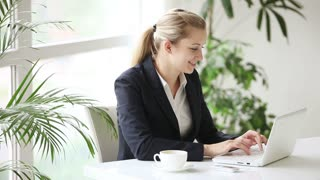 Attractive young businesswoman at office using laptop and talking on phone