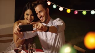 Attractive young couple posing for a selfie on their mobile phone as they celebrate together at a party with colorful lights in the background