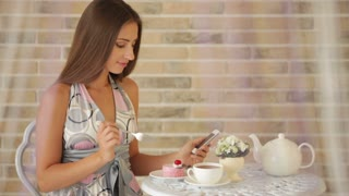 Attractive young girl sitting at cafe and using cellphone and eating cake