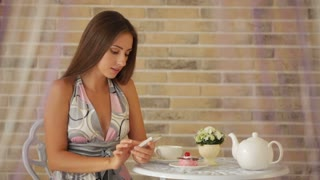 Attractive young girl sitting at cafe and using cellphone