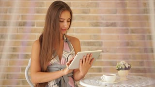 Attractive young girl sitting at cafe with cup of tea and using tablet
