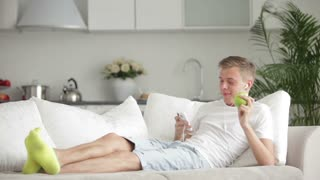 Attractive young man lying on sofa using cell phone and eating apple