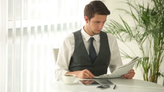 Attractive young man sitting at table drinking coffee and reading newspaper