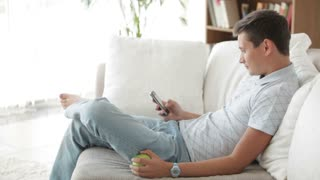 Attractive young man sitting on sofa using cellphone and eating apple