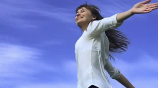 Attractive young woman dancing outdoors on a blue sky background. Slow motion, shot at 240 fps. Dolly shot. Woman turning around and smiling, feeling happy and free.
