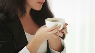 Attractive young woman enjoying coffee smiling and looking at camera