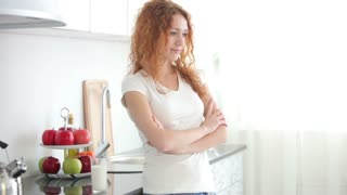Attractive young woman in kitchen drinking milk from glass and smiling