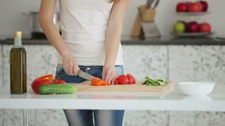 Attractive young woman in kitchen slicing vegetables on cutting board and smiling at camera