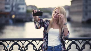 Attractive young woman is taking selfie on the black bridge cross the water canal, charming smile and sexy look. The city-river and beautiful buildings on the background. Evening time, sunset.