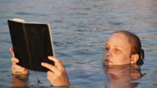 Attractive young woman reading a book while floating on her back in a tranquil sea