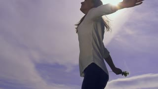 Attractive young woman silhouette dancing outdoors on a sunset with sun shining bright behind her on a horizon. Slow motion, shot at 240 fps.