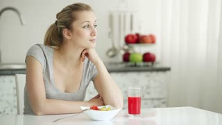 Attractive young woman sitting at kitchen table with bowl of vegetable salad and glass of juice and smiling