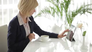 Attractive young woman sitting at office table using touchpad drinking tea and smiling at camera