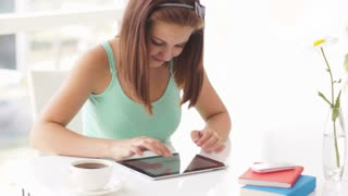 Attractive young woman sitting at table using touch pad and smiling at camera