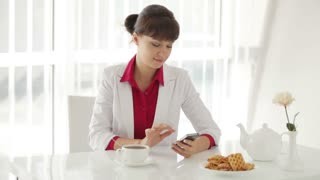 Attractive young woman sitting at table with cup of tea and using cellphone