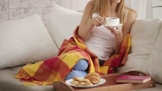 Attractive young woman sitting on sofa drinking tea looking at camera and smiling. Panning camera