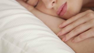 Attractive young woman sleeping in bed waking up looking at camera and smiling. Panning camera